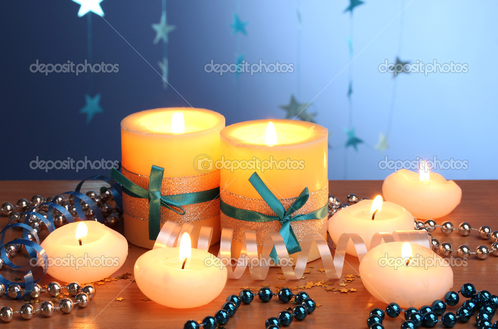 Beautiful candles, gifts and decor on wooden table on blue background — Stock Photo #8931371