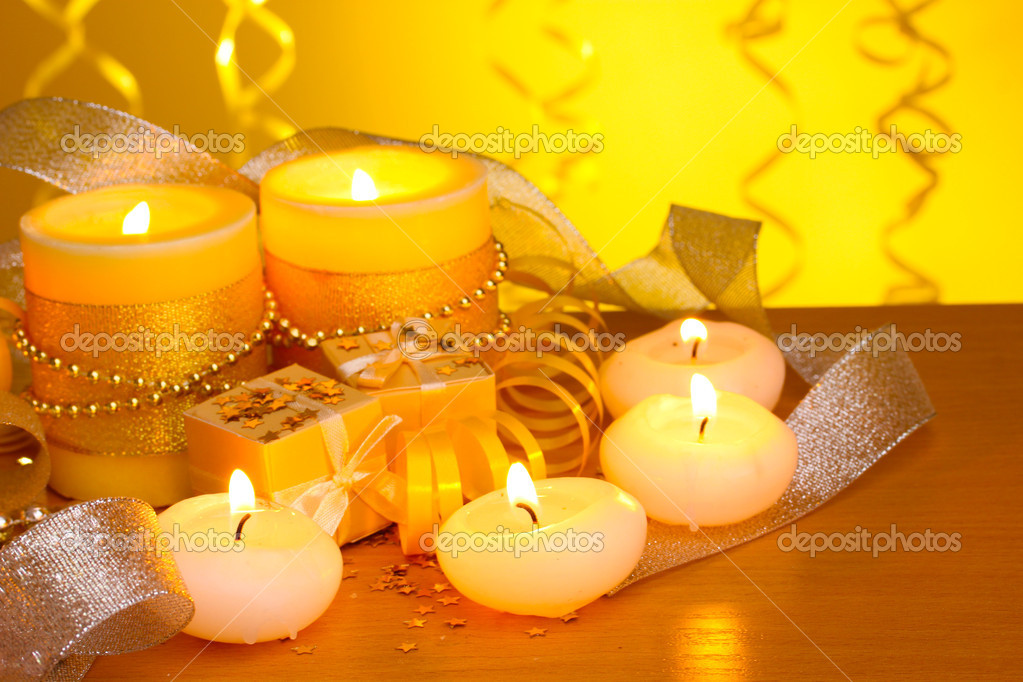 Beautiful candles, gifts and decor on wooden table on yellow background — Stock Photo #8931376