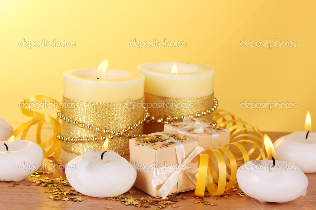 Beautiful candles, gifts and decor on wooden table on yellow background — Stock Photo #8937218