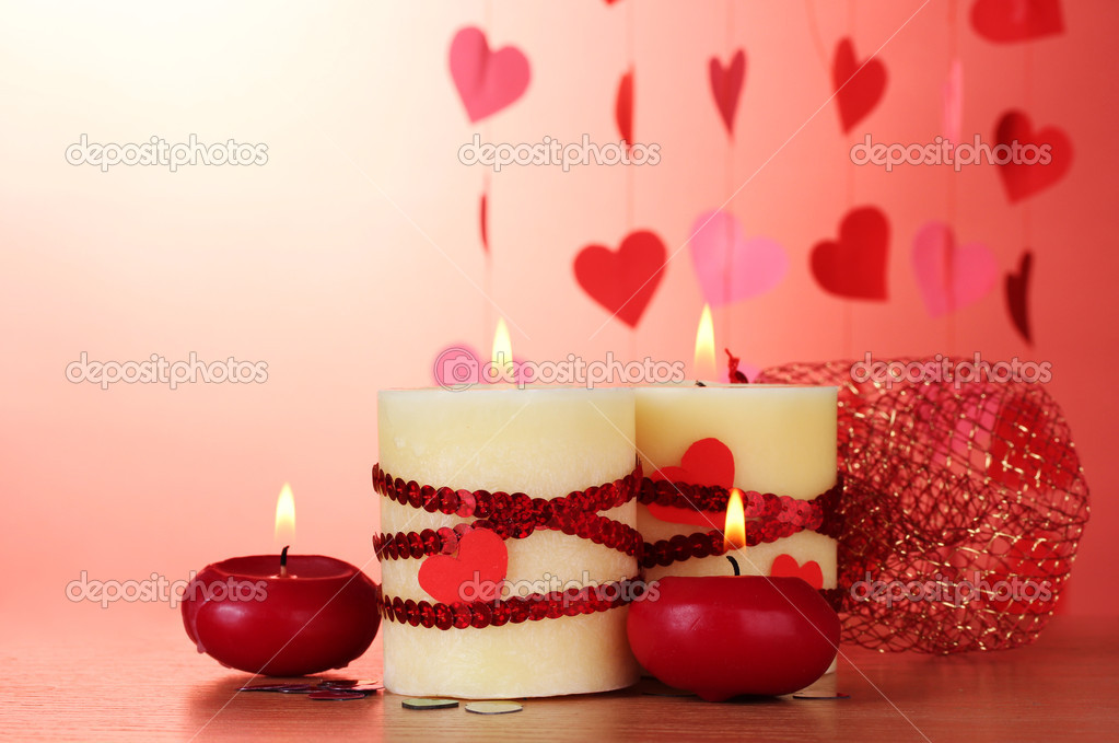 Candles for Valentine's Day on wooden table on red background — Stock Photo #8937245