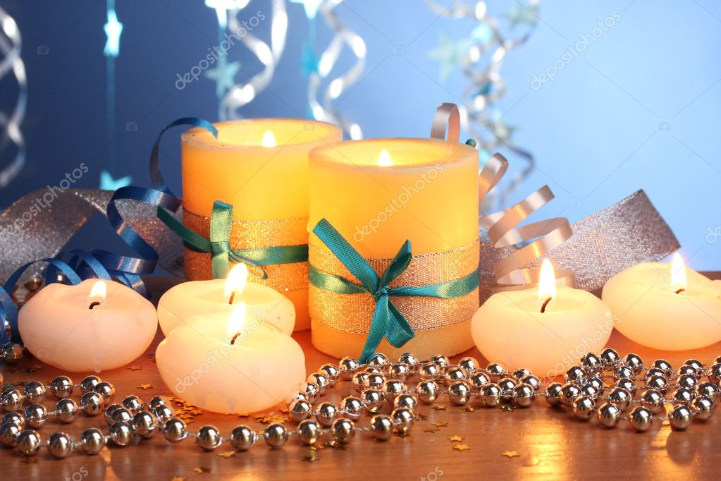 Beautiful candles, gifts and decor on wooden table on blue background — Stock Photo #8937249