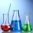 Three flasks with color liquid with reflection on blue background — Stock Photo
