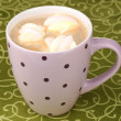Cup of cappucino with marshmallows on green tablecloth — Stock Photo #8956228