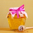 Stock Photo: Jar of honey and wooden drizzler on yellow honeycomb background