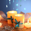 Beautiful candles, gifts and decor on wooden table on blue background — Photo