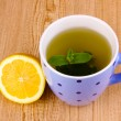 Mint tea with mint leaf and lemon on wooden background - Stock Photo