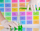 Laboratory flask and tube with green liquid in scientist's hands on co — Stock Photo