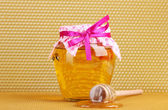 Jar of honey and wooden drizzler on yellow honeycomb background — Stock Photo