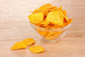 Tasty potato chips in transparent bowl on wooden table — Stock Photo