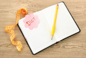 Planning of diet. Notebook measuring tape and pen on wooden table — Stock Photo