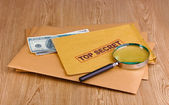 Envelopes with top secret stamp with magnifying glass and money on wooden b — Stock Photo