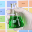 Flask with green liquid in hand on color samples background - Stock Photo