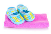 Blue baby booties on pink towel isolated on white — Stock Photo