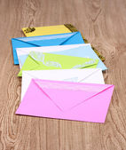 Bunch of color envelopes on wooden background — Stock Photo