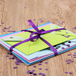 Stock Photo: Bunch of color envelopes with ribbon and confetti on wooden background