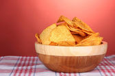 Tasty potato chips in wooden bowl on napkin on red background — Stock Photo