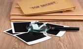 φάκελοι με κορυφαίο μυστικό σφραγίδα με φωτογραφικά χαρτιά και μεγεθυντικό φακό σε w — Φωτογραφία Αρχείου