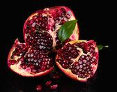 Ripe pomegranate fruit with leaves on black background — Stock Photo