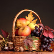 Beautiful autumn harvest in basket and leaves on brown background - Stockfoto