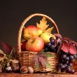 Beautiful autumn harvest in basket and leaves on brown background - Photo