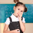 Beautiful little girl standing near blackboard in the classroom — Foto Stock
