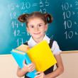 Beautiful little girl with books standing near blackboard in classroom — Foto de Stock