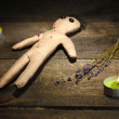 Voodoo doll boy on a wooden table in the candlelight - Foto Stock