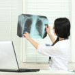 Beautiful girl doctor holding X-ray in the office — Stock Photo