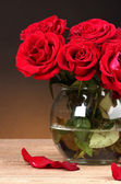 Beautiful red roses in vase on wooden table on brown background — Stock Photo