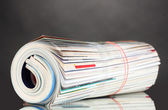 Rolled up magazines on gray background — Stock Photo