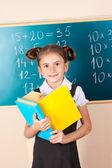 Beautiful little girl with books standing near blackboard in classroom — Stock Photo