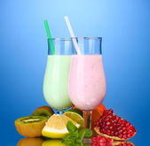 Milk shakes with fruits on blue background — Stock Photo