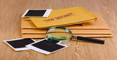 Envelopes with top secret stamp with photo papers and magnifying glass on w — Stock Photo