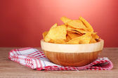 Tasty potato chips in wooden bowl on wooden table on red background — Stock Photo