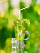 Glass of cocktail with lime and mint on green background — Stock Photo