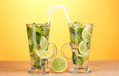 Glasses of cocktail with lime and mint on wooden table on yellow background — Stock Photo