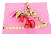 Scissors, treads and measuring tape on fabric isolated on white — Stock Photo