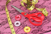 Scissors, buttons, measuring tape and pattern on fabric — Stock Photo