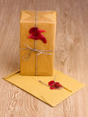 Parcel and envelope with sealing wax on wooden background — Stock Photo