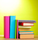 Books with stationery on wooden table on green background — Stockfoto