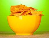 Microplaquetas de batata saborosas tigela amarela na mesa de madeira sobre fundo verde — Foto Stock