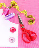 Scissors, threads, buttons, measuring tape and pattern on fabric isolated o — Stock Photo
