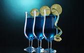 Bandejas de papel brillante y papelería en mesa de madera sobre fondo azul — Foto de Stock