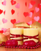 Beautiful candles with romantic decor on a wooden table on a red background — Stock Photo
