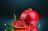 Ripe pomegranate fruit with leaves on blue background — Stock Photo