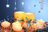 Mooie kaarsen, geschenken en decor op houten tafel op blauwe achtergrond — Stockfoto