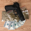 Marihuana in packages, dollars and handgun on wooden background - Stock Photo