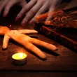 Foto Stock: Voodoo doll boy on wooden table in candlelight