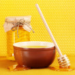 Jar of honey, bowl and wooden drizzler with honey on yellow honeycomb backg - Zdjęcie stockowe