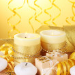 Beautiful candles, gifts and decor on wooden table on yellow background — Stock Photo #9134973